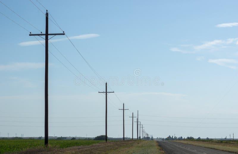 Landstraße im leeren Texas-Grasland mit einer endlosen Ausdehnung des blauen Himmels und der Stromleitungen stockfoto