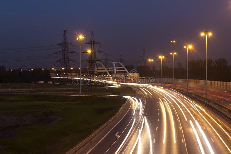 Landstraße mit Autolichtspuren stockbild