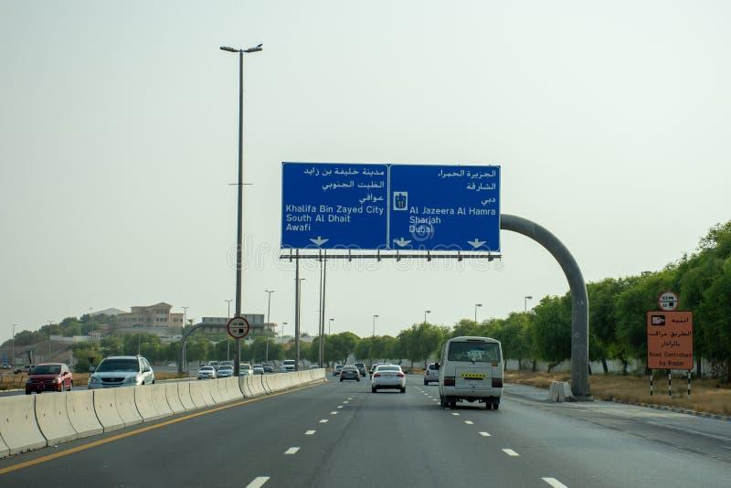 Landstraße in RAK auf dem E11, das ein Zeichen zu Al Dhait oder zu Al Jazeera Al Hamra an einem ruhigen Sommernachmittag betracht lizenzfreie stockfotografie