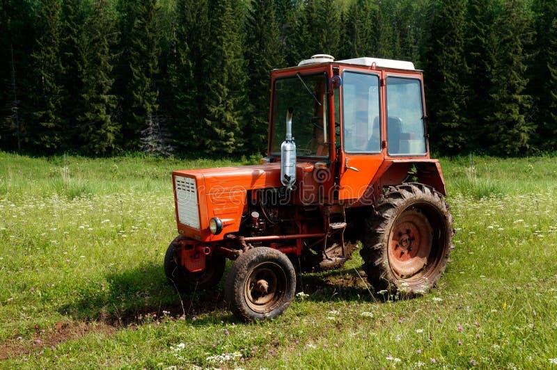 Landstraße und ein Traktor auf dem Gebiet an einem Sommertag lizenzfreie stockbilder