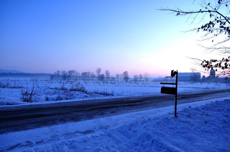 Landstraße und schneebedeckte plaines, Briefkasten und Bauernhof stockbilder