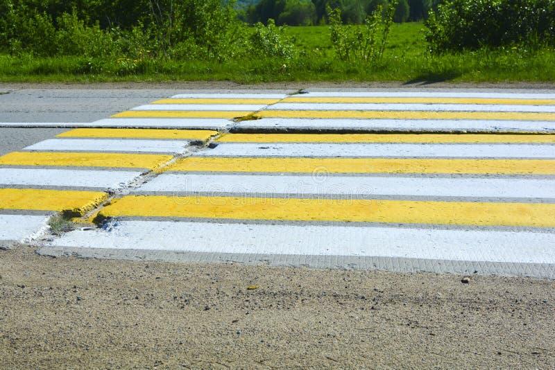 Landstraße von Betonplatten Fußgängercrossing over eine Betonstraße Weiße und gelbe Streifen auf der Straße lizenzfreies stockfoto