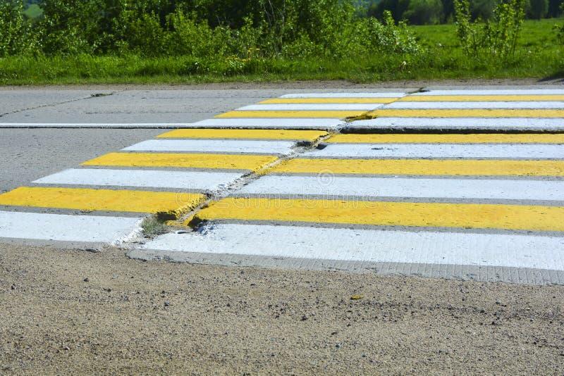 Landstraße von Betonplatten Fußgängercrossing over eine Betonstraße Weiße und gelbe Streifen auf der Straße stockfoto