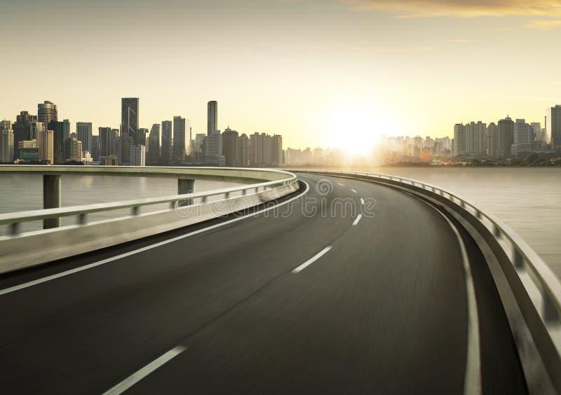 Landstraßenüberführungsbewegungsunschärfe mit Stadtskyline backgroun lizenzfreies stockbild
