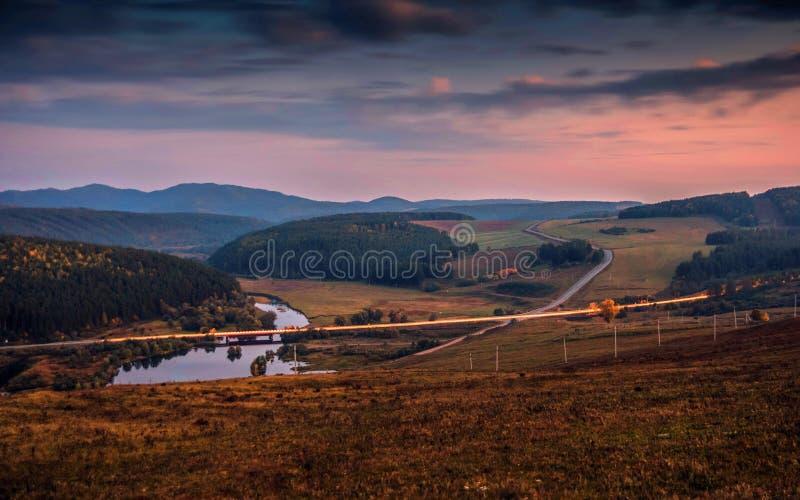Landstraßen- und Straßenbrücke über dem Fluss an der Sonnenuntergangabendsonne auf dem Hintergrund der Berge stockfoto