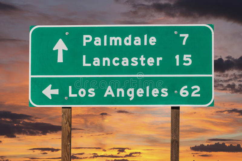 Landstraßen-Zeichen Palmdale, Lancasters und Los Angeless mit Sonnenuntergang-Himmel stockfoto