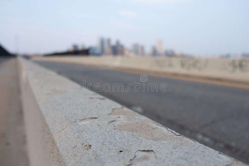Landstraßenseitenwand mit unscharfer Stadt im Hintergrund stockbild
