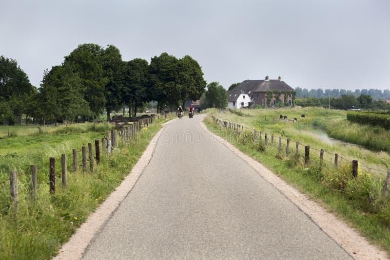 Landsväg med cyklister i avståndet arkivbilder