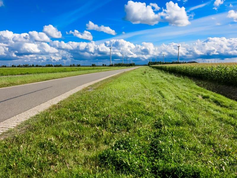 Landsväg med vindturbiner i polder, Nederländerna arkivbild