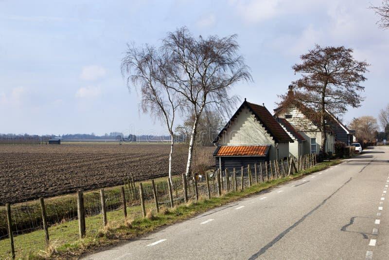 Landsväg och ett plogat fält i holländskt polderlandskap royaltyfri foto