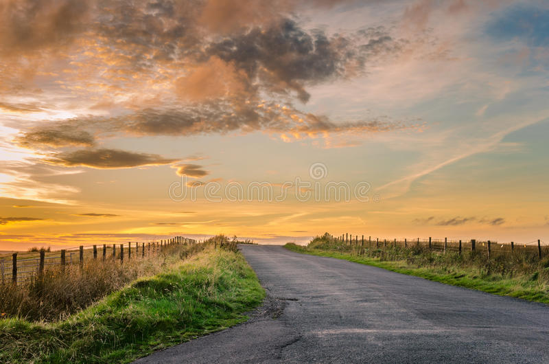 Landsväg på solnedgången arkivbilder