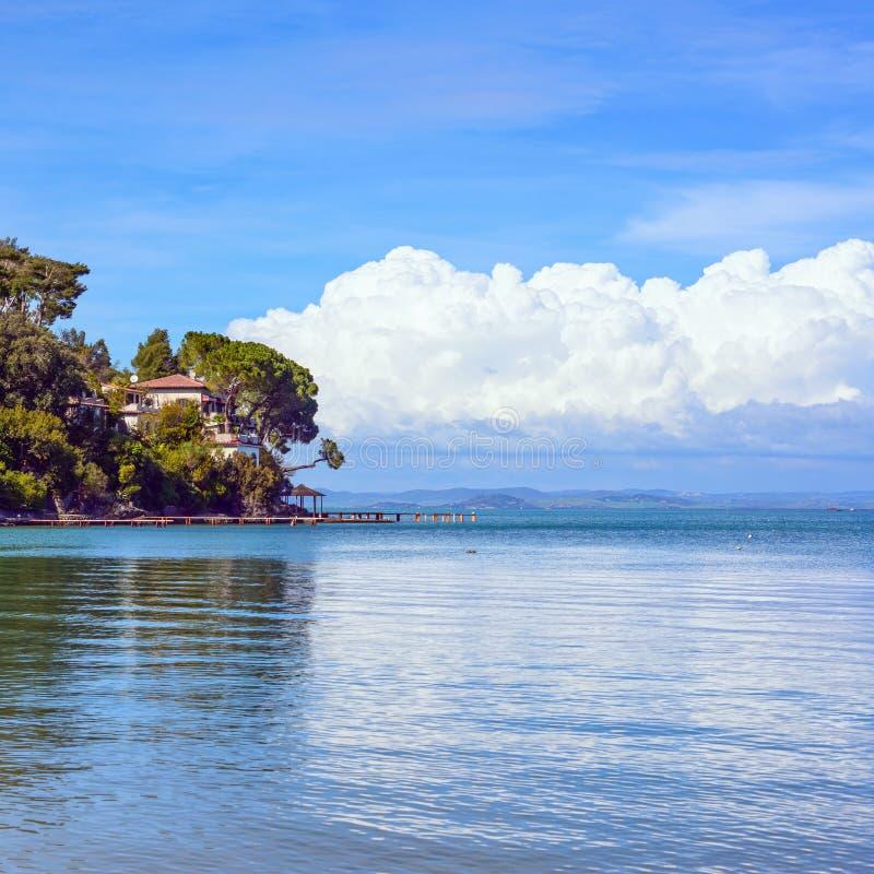 Landtong, bomen, en pijler of pier op een blauwe oceaan. Strand in Argentario, Toscanië, Italië stock foto's