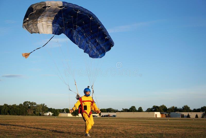 Landung eines parachuter vor dem hintergrund der Wälder und der BU lizenzfreie stockfotografie