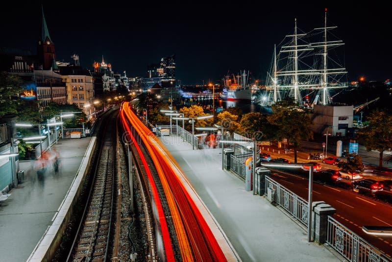 Landungsbruecken在汉堡在晚上 从火车运动的令人惊讶的轻的足迹 港口和地铁都市都市风景  图库摄影