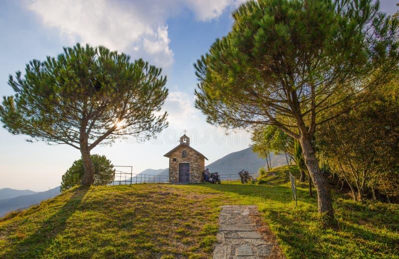 Landweg bergopwaarts door de bomen en een kleine kerk stock fotografie
