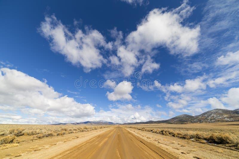 Landweg in de woestijn van Nevada onder blauwe hemel met wolken stock fotografie