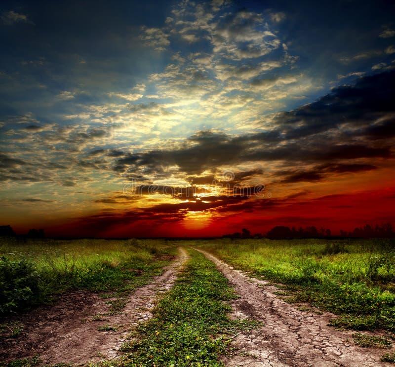 Landweg en zonsondergang royalty-vrije stock afbeelding