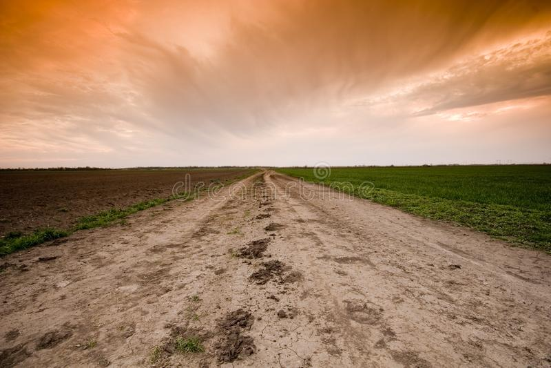Landweg en zonsondergang stock afbeelding