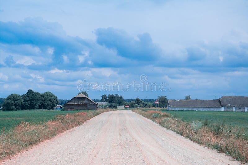 Landweg in gebied en blauwe hemel stock afbeeldingen