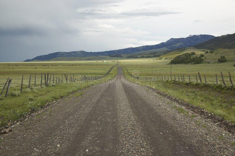 Landweg in Honderdjarige Vallei, Montana met inkomend onweer, groene gebieden en bergen stock foto
