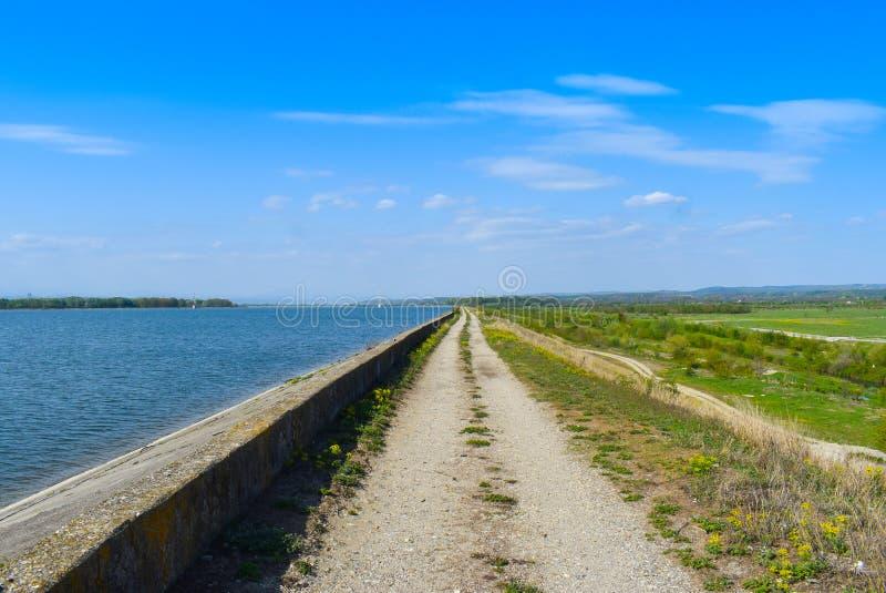 Landweg langs de meerdam in een zonnige de zomerdag met perfecte blauwe hemel stock afbeelding