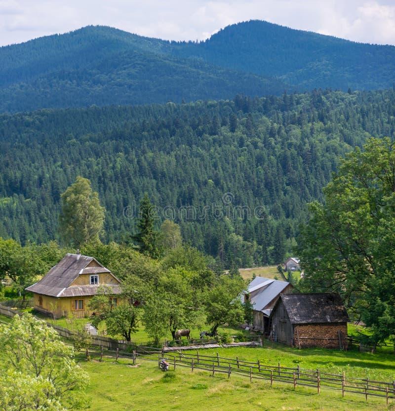 Landweg, omheining, dorpshuizen en bergpieken royalty-vrije stock foto