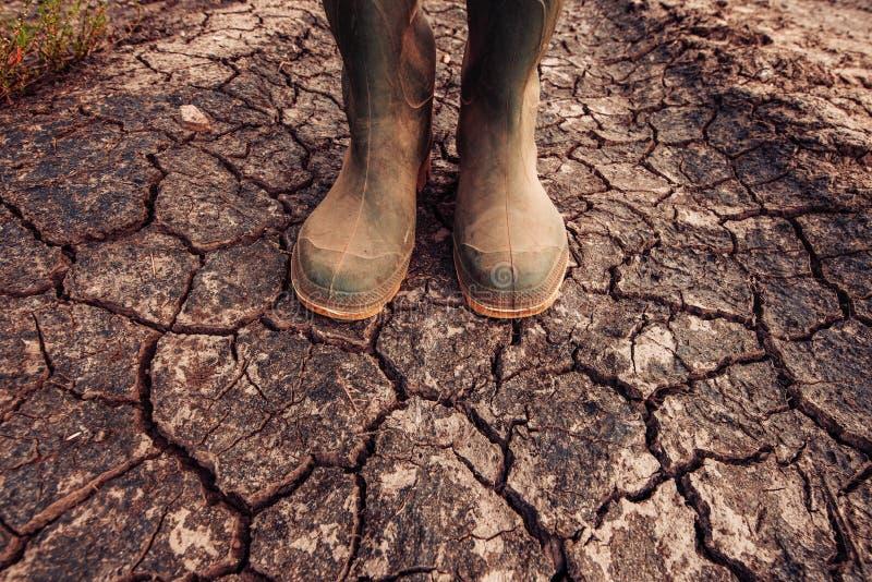 Landwirt in den Gummistiefeln, die auf Boden des trockenen Bodens stehen lizenzfreies stockfoto