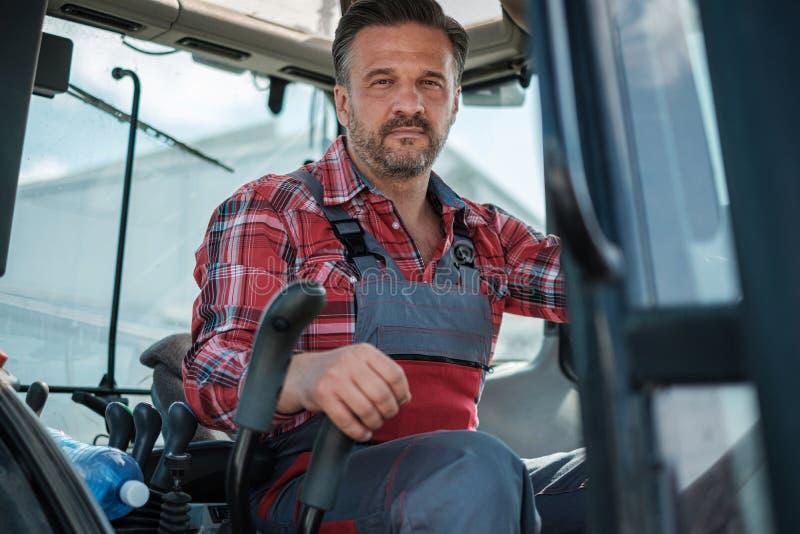 Landwirt, der an einem modernen Traktor arbeitet stockbilder
