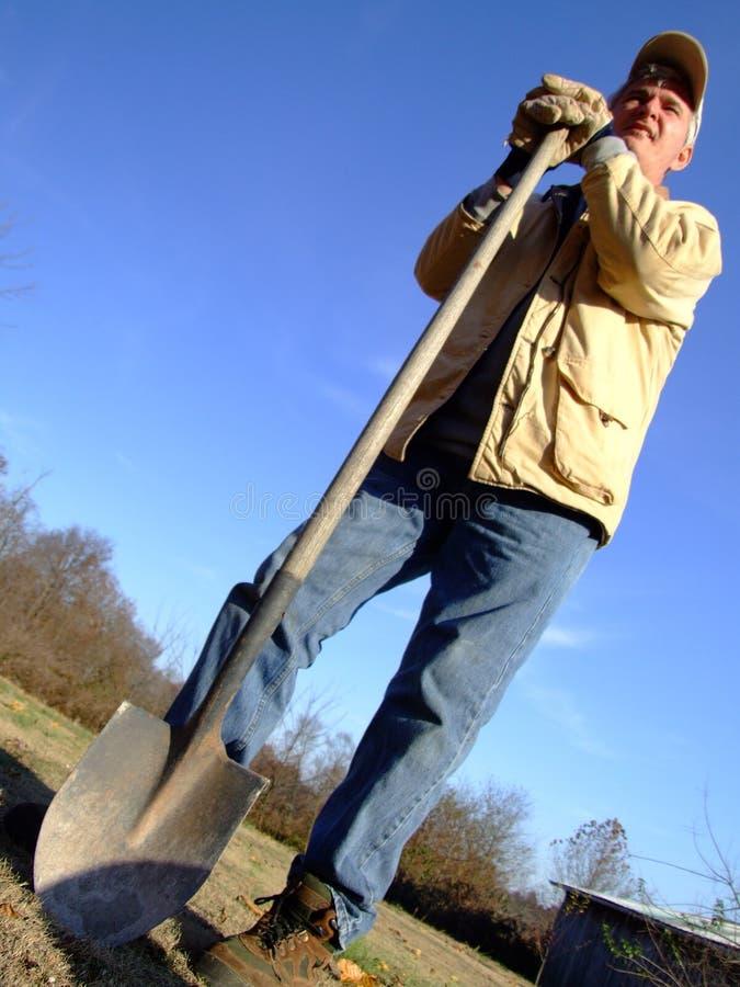 Landwirt, der mit Schaufel steht stockfotos