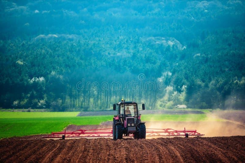 Landwirt im Traktor, der Land mit Saatbeetlandwirt vorbereitet stockfotos