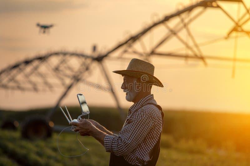 Landwirt mit Brummen auf dem Gebiet mit Bewässerungssystem lizenzfreie stockfotos