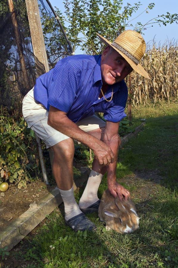 Landwirt mit seinem Kaninchen lizenzfreie stockbilder