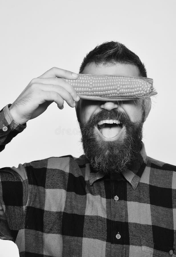 Landwirt mit verstecktem fröhlichem Gesicht mit gelber Maisbedeckung mustert lizenzfreie stockbilder