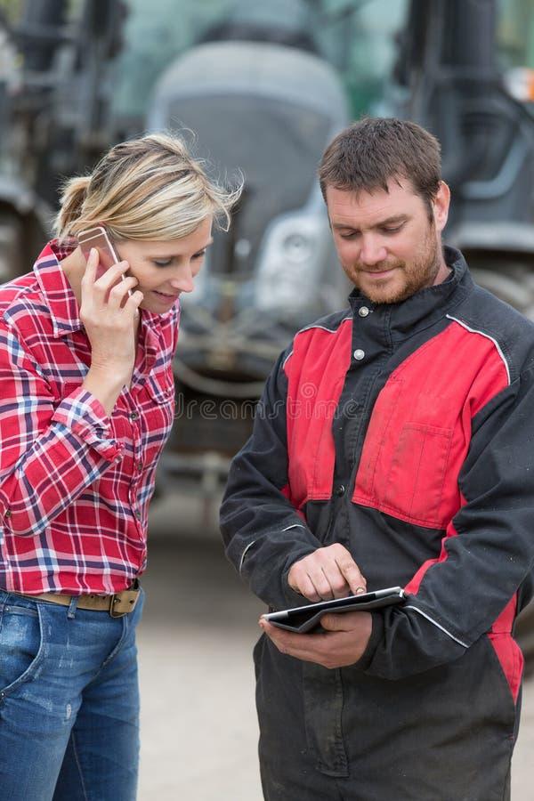 Landwirt und Techniker, die zusammen mit Elektronik arbeiten lizenzfreies stockbild