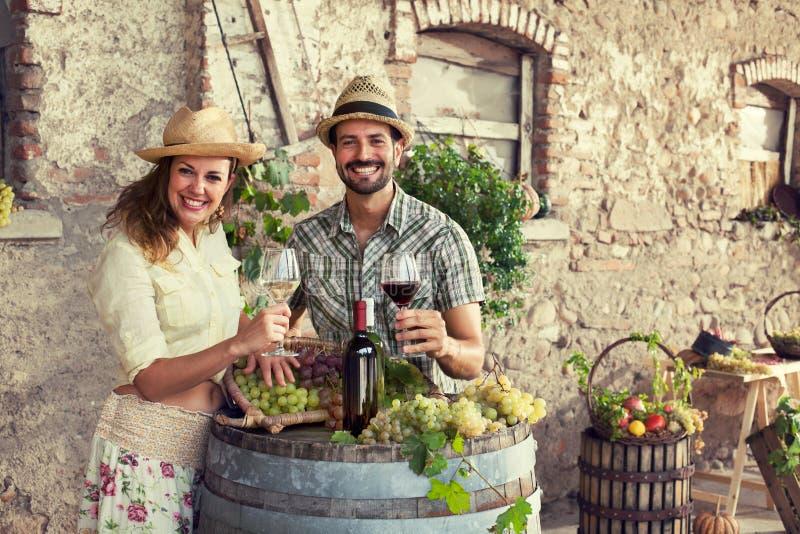 Landwirte verbinden trinkenden Wein in einem Bauernhof lizenzfreie stockbilder