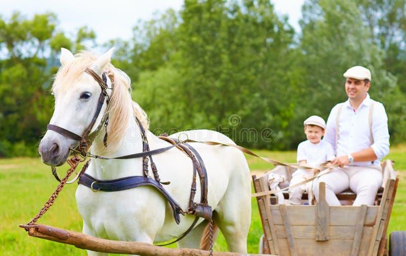 Landwirtfamilie, die einen Pferdewarenkorb reitet Fokus auf Pferd lizenzfreies stockbild