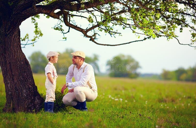 Landwirtfamilie, die Spaß unter einem alten Baum, Frühlingslandschaft hat stockfotos