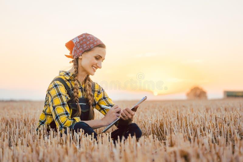 Landwirtfrau, die Ernteertrag nach einem langen Tag berechnet lizenzfreie stockfotos