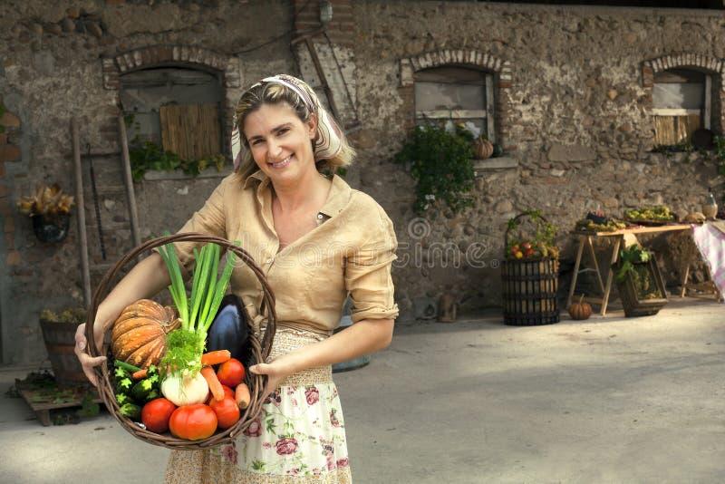 Landwirtfrau, welche die Landprodukte gerade aufgehoben zeigt stockfotos