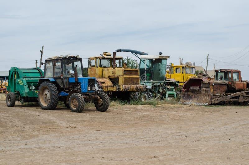 Landwirtschaftliche Maschinerie wie Traktor, Pflug, Eggenstände auf dem Gebiet stockfotografie