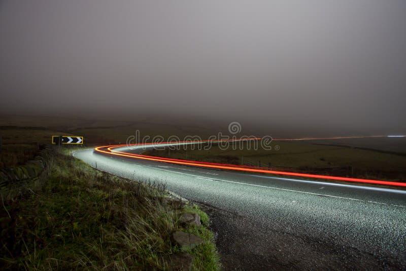 Landwirtschaftliche Straße nachts im Nebel - Katze und Geige lizenzfreies stockfoto