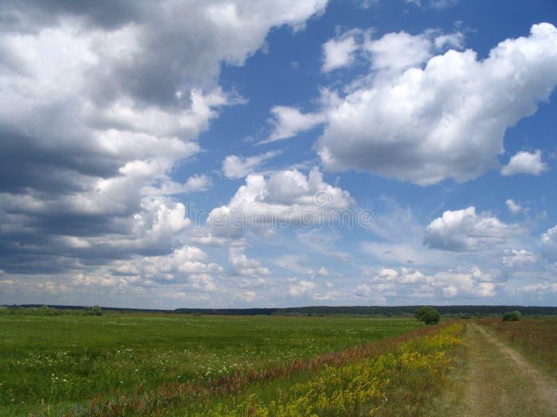 Landwirtschaftliche Straße und Wolken stockfotografie