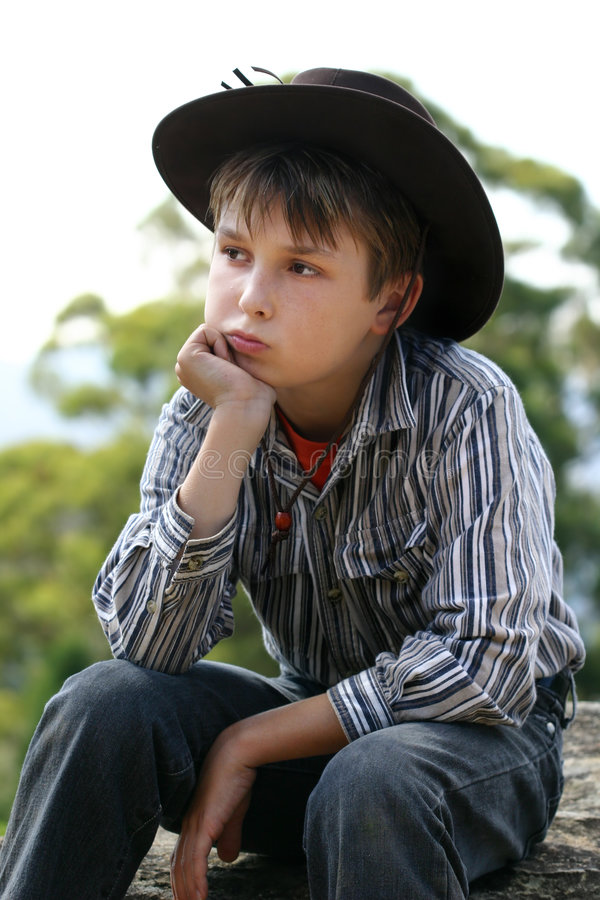 Landwirtschaftlicher Junge, der auf einem Felsen sitzt lizenzfreies stockfoto
