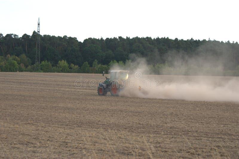Landwirtschaftlicher Traktor, der ein Feld während der Sommerdürre von 2018 in Deutschland eggt stockfoto