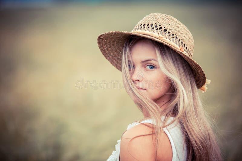 Landwirtschaftliches Mädchen in einem Strohhut lizenzfreie stockfotos