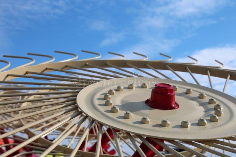 Landwirtschaftliches Werkzeug, zum des Schnittgrases mit dem blauen Himmel zu drehen stockfotos