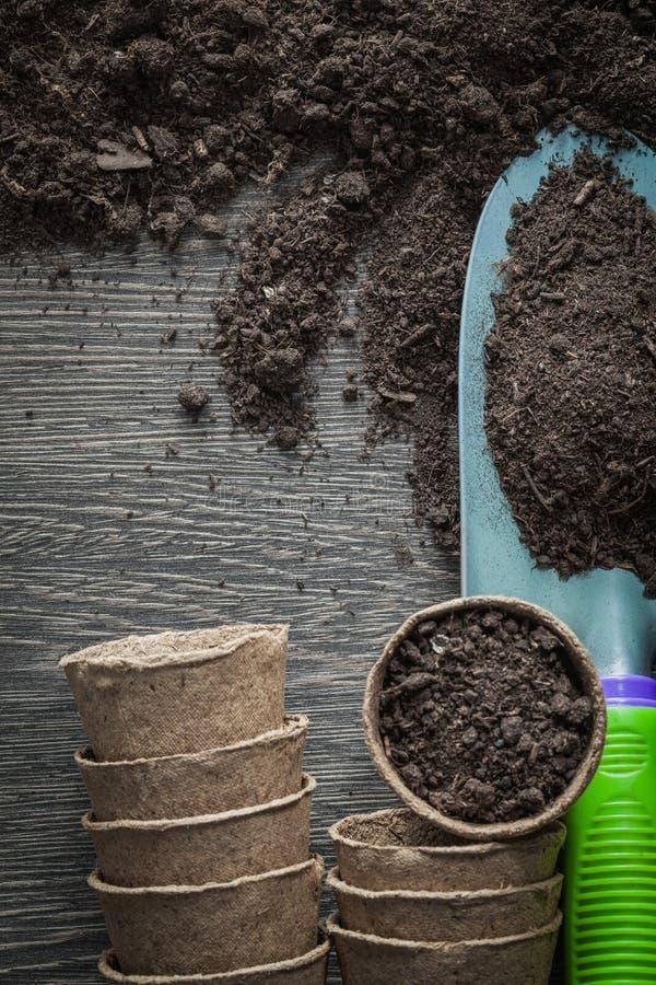 Landwirtschaftstorftöpfe beschmutzen Schaufel auf hölzernem Brett lizenzfreie stockfotos