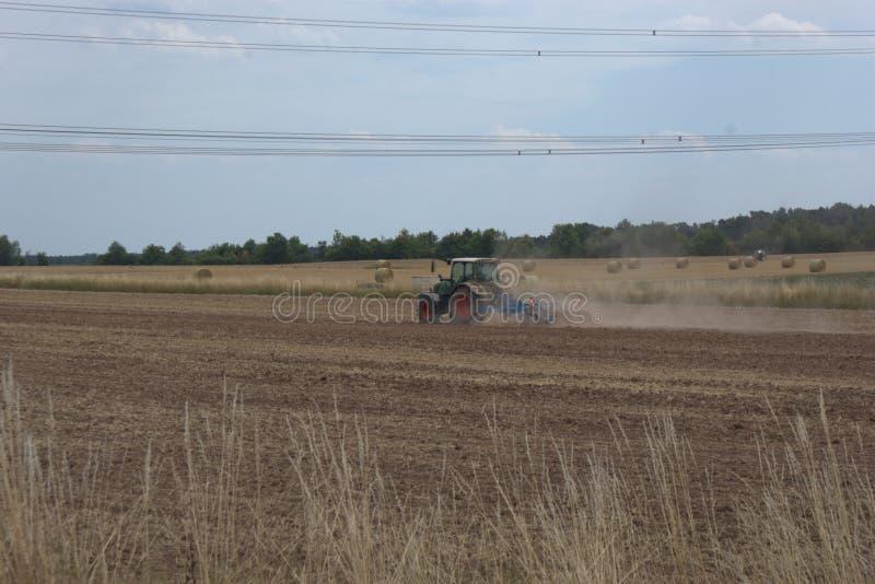 Landwirtschaftstraktor, der ein trockenes Feld, nach einer Sommerernte eggt und oben viel Staub vom trockenen Ackerland wirft lizenzfreies stockbild