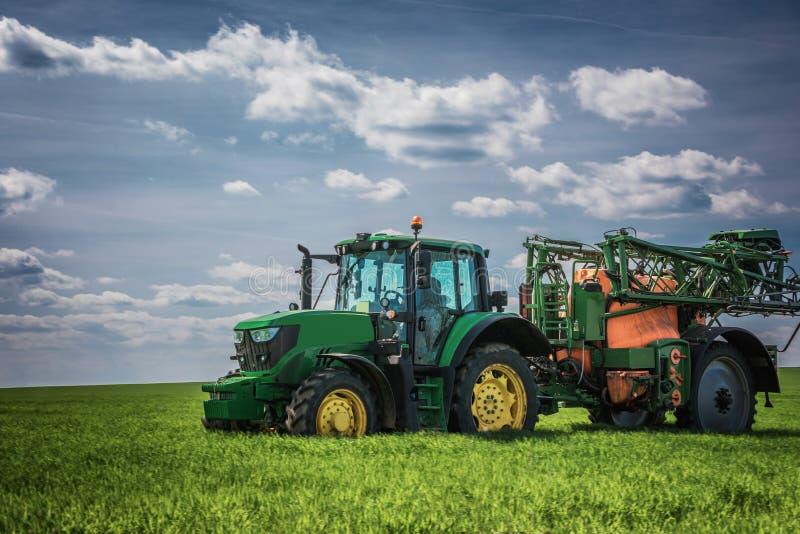 Landwirtschafttraktor, der auf Feld pflügt und sprüht lizenzfreies stockbild
