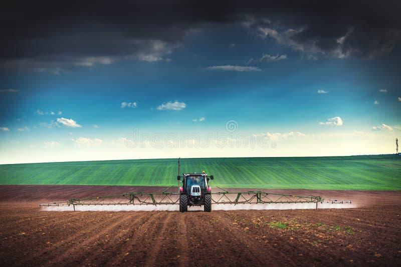 Landwirtschafttraktor, der auf Feld pflügt und sprüht stockbilder